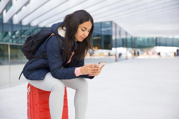 Serious busy young woman using smartphone in airport Free Photo