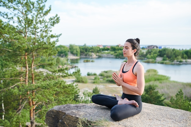 湖の石の蓮華座に座っていると瞑想しながらナマステジェスチャーを作る深刻な穏やかな若い女の子 Premium写真