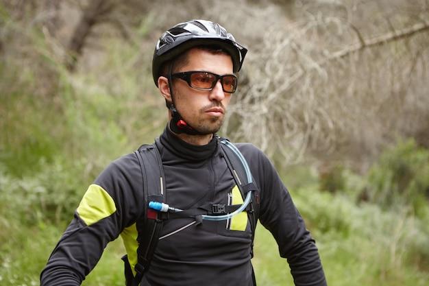 保護用のヘルメットとメガネを身に着けている深刻な白人男性サイクリスト 無料写真