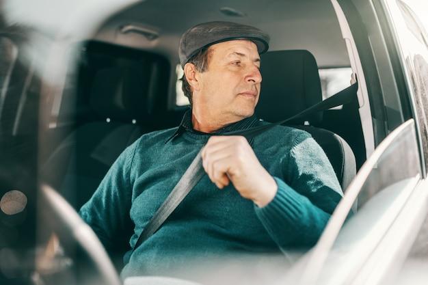 車の中で座っているとシートベルトを締める頭の上のキャップを持つ深刻な白人シニア男性 Premium写真