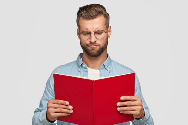 Giovane insegnante maschio intelligente serio con taglio di capelli alla moda, trasporta il libro rosso, loos esitante Foto Gratuite