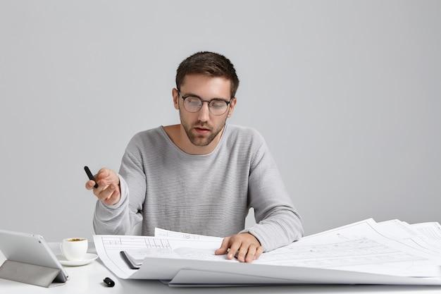 真剣に集中した男性デザイナーがルーズなセーターと丸いメガネをかけ、スケッチを注意深く見る 無料写真