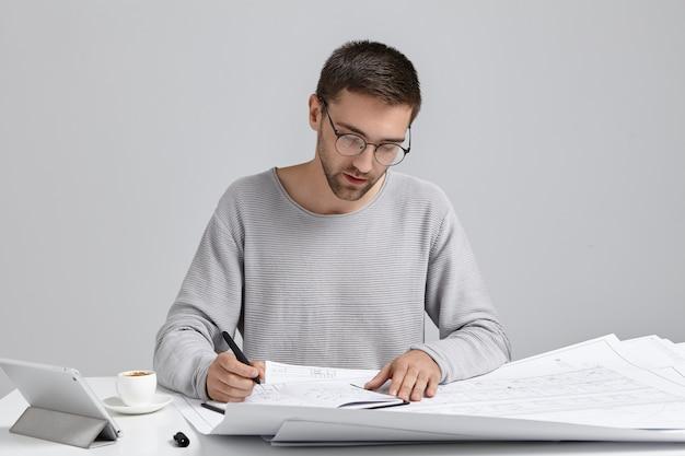 심각한 집중 남자 스케치 그리기, 청사진 준비, 현대 태블릿 사용 무료 사진