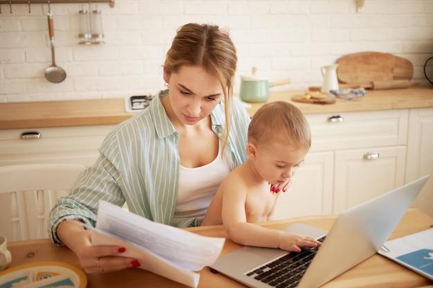 Серьезная сконцентрированная молодая женщина изучает документы в руках, оплачивает счета онлайн, сидит за кухонным столом перед открытым ноутбуком, держа маленького сына на коленях. маленький ребенок, печатающий на портативном компьютере Бесплатные Фотографии