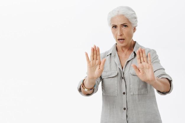 La nonna preoccupata seria che alza le mani in su nel gesto di arresto, dica di calmarsi Foto Gratuite