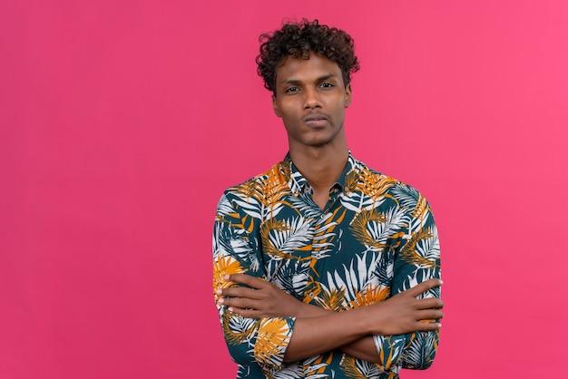 Uomo serio fiducioso di carnagione scura con capelli ricci in foglie camicia stampata tenendo le mani giunte mentre guarda la fotocamera su uno sfondo rosa Foto Gratuite
