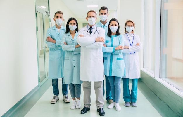 腕を組んで安全医療マスクの深刻な自信を持っている医師チームが病院の背景にカメラを見ています Premium写真