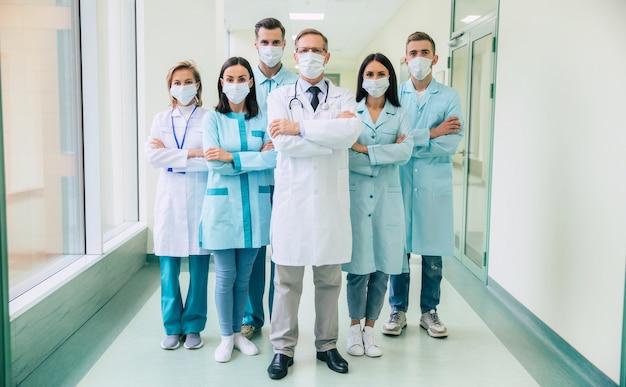 Команда серьезных уверенных врачей в защитных медицинских масках со скрещенными руками смотрит в камеру на фоне больницы Premium Фотографии