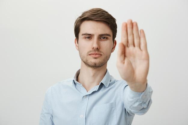 Серьезный уверенный в себе мужчина протягивает руку к остановке магазина, предупреждению или ограничению Бесплатные Фотографии