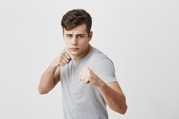 Serious confident muscular young sportsman frowns face in displeasure, shows clenched fists, demonstrates strength and irritation, ready to defend himself. power and strenght concept. Free Photo