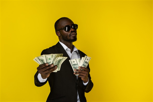 Serious and cool man shows the money Free Photo