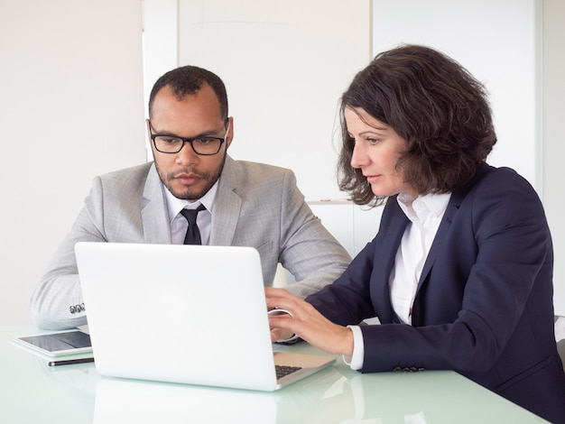 Serious coworkers using laptop Free Photo
