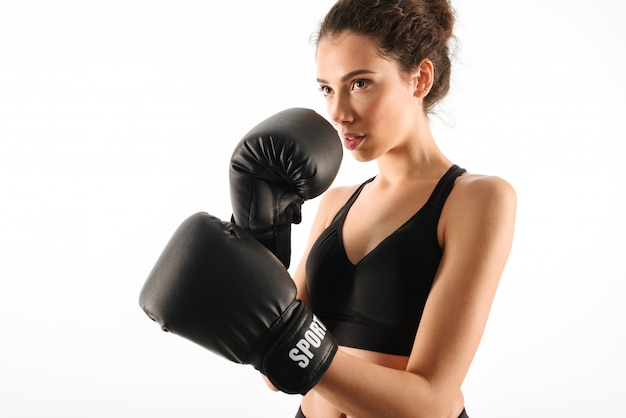 Serious curly brunette fitness woman in boxing gloves Free Photo