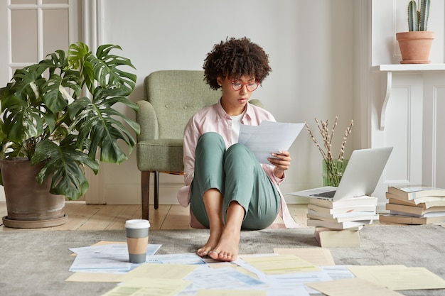 Serious dark skinned female worker hipster waits for update installation on laptop computer, sits on floor with many papers Free Photo