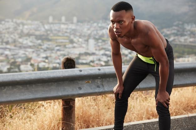 Un uomo sano e serio dalla pelle scura ha determinato l'espressione del viso, tiene le mani sulle ginocchia, posa in topless da solo sulla strada di montagna, ha una forma del corpo atletica Foto Gratuite