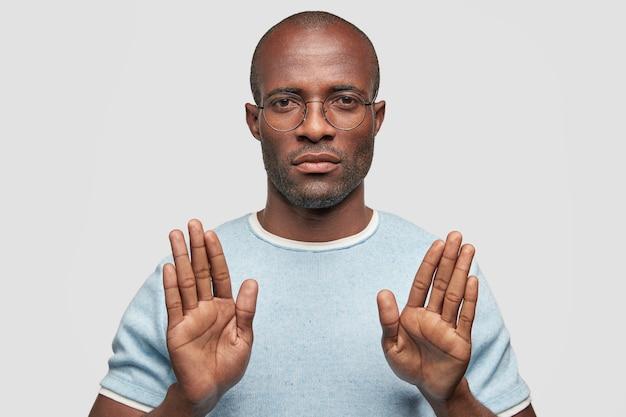 Grave maschio dalla pelle scura mostra il gesto di arresto Foto Gratuite