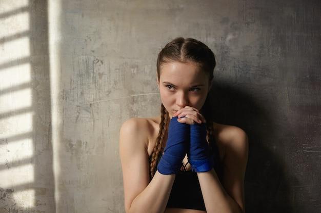 Grave e determinata ragazza adolescente con due trecce in posa in bianco parete testurizzata, indossando bende blu, stringendo le mani sul viso, pronto per la lezione di boxe Foto Gratuite