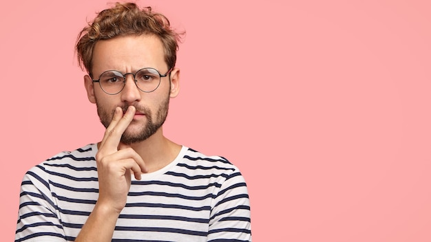 Serious displeased man frowns face, keeps hand on mouth, has curly hair and stubble, wears striped t shirt, round spectacles Free Photo