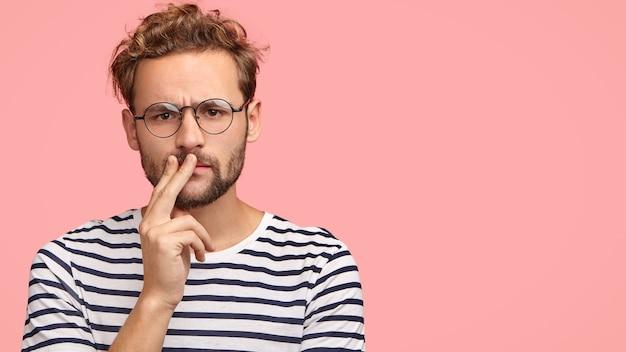 深刻な不機嫌な男は顔をしかめ、口に手を保ち、巻き毛と無精ひげを持ち、縞模様のtシャツを着て、丸い眼鏡をかけています 無料写真