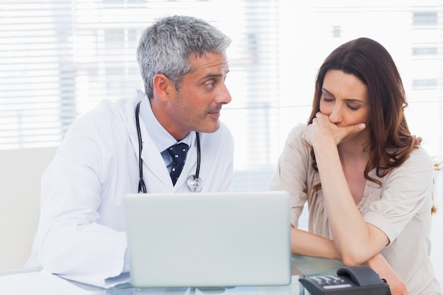 Serious docter showing something on laptop to his patient Premium Photo