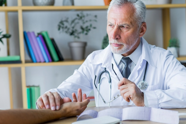 Serious doctor checking pulse of patient Free Photo