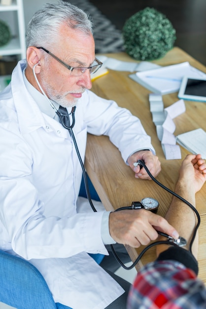 Serious doctor measuring blood pressure of patient Free Photo