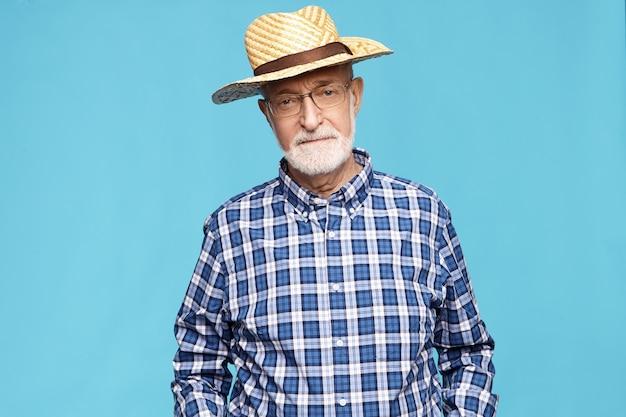 Серьезный пожилой пенсионер с седой бородой, проводящий лето в сельской местности, позирует изолированно, в синей клетчатой рубашке и соломенной шляпе. пожилые люди, зрелый возраст, образ жизни и пенсия Бесплатные Фотографии