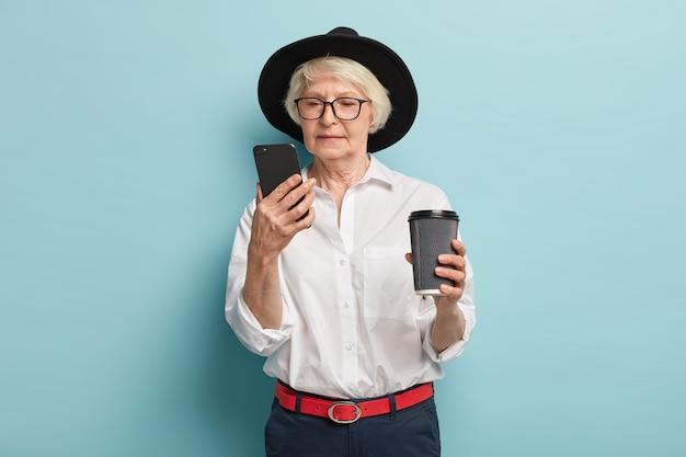スマートフォンデバイスに焦点を当てた深刻な年配の女性、インターネットで情報を検索し、オンラインで記事を読み、コーヒーを飲みに行き、退職者のための簡単なアプリケーションを使用し、スタイリッシュな服を着て、屋内でポーズをとる 無料写真