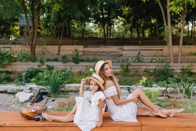 娘と一緒に歩いた後、ベンチに座って、彼女の足に触れて、白いドレスを着た真面目でエレガントな女性。公園と一緒にポーズをとってロマンチックな若いお母さんと帽子の少女の屋外の肖像画。 無料写真