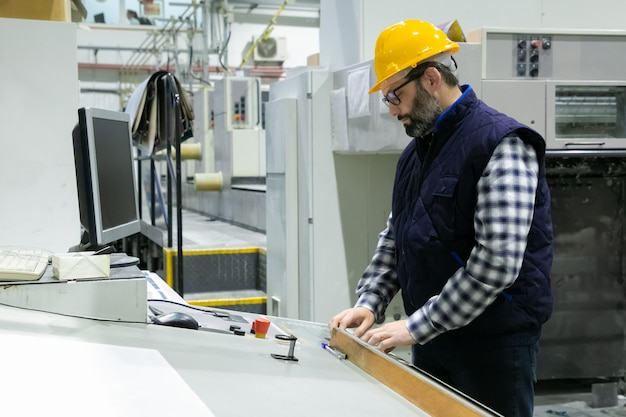 Serious engineer in glasses operating machine Free Photo