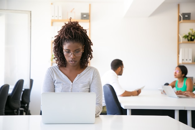 Serious excited african american employee working on computer Free Photo
