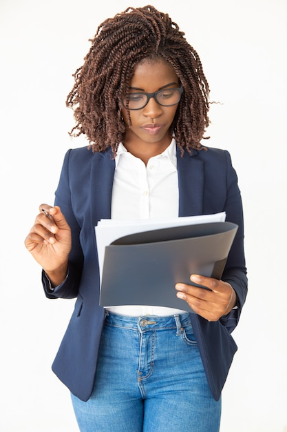 Serious expert wearing glasses, reading document Free Photo