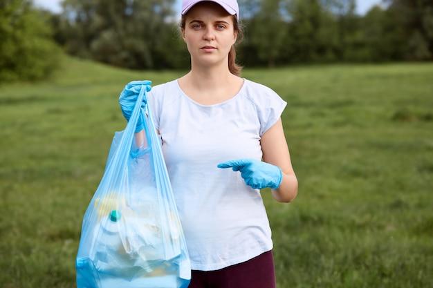Donna seria in berretto da baseball e maglietta, signora con sacco della spazzatura in una mano Foto Gratuite