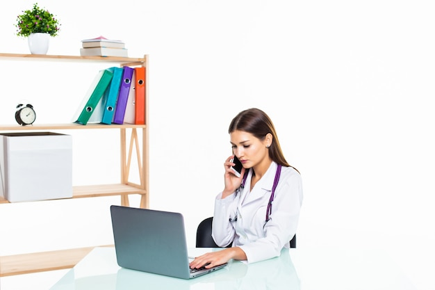 Серьезная женщина-врач сидит за партой во время разговора с кем-то по телефону и с помощью своего ноутбука Бесплатные Фотографии