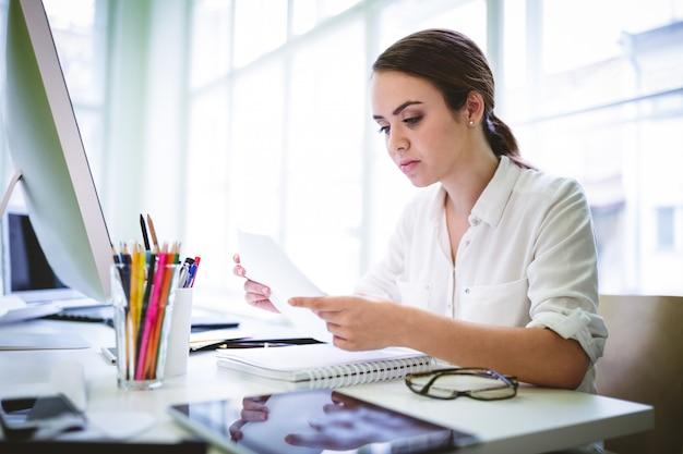 Serious female graphic designer reading document Premium Photo