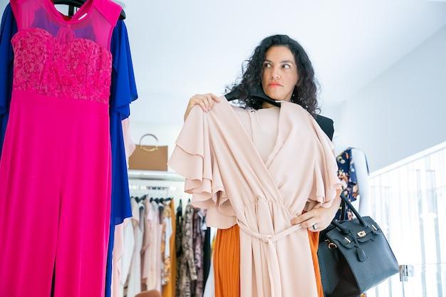 Cliente femminile serio che tiene il gancio con il panno, applicando il vestito a se stessa, distogliendo lo sguardo. vista frontale. negozio di moda o concetto di vendita al dettaglio Foto Gratuite