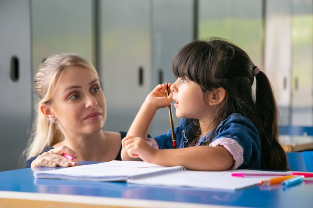 Serious female teacher discussing task with little pupil Free Photo