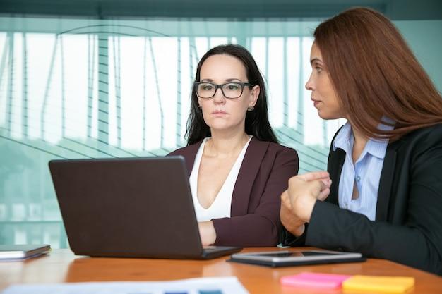 深刻な焦点を当てたビジネスの女性が会議のテーブルに座っている間、プロジェクトについて話し合い、ラップトップを使用しています。 無料写真