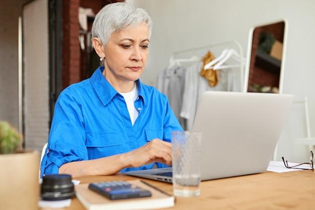 Серьезная сосредоточенная домохозяйка средних лет, одетая в синюю рубашку, работает с портативным компьютером, оплачивая счета за электричество, газ и коммунальные услуги онлайн, сидя за столом с калькулятором. выборочный фокус Бесплатные Фотографии
