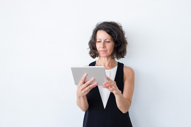Serious focused woman in casual using tablet Free Photo