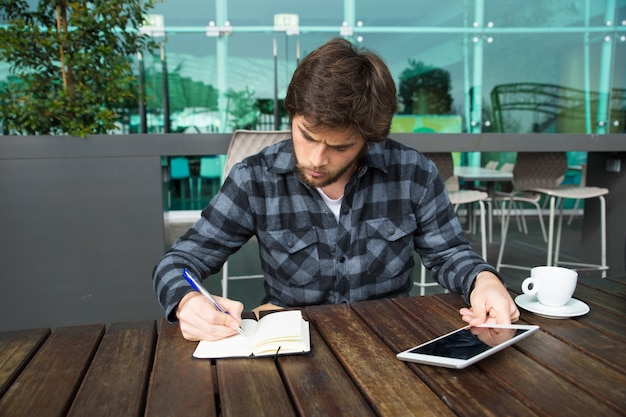 Serious freelancer working in outdoor cafe Free Photo