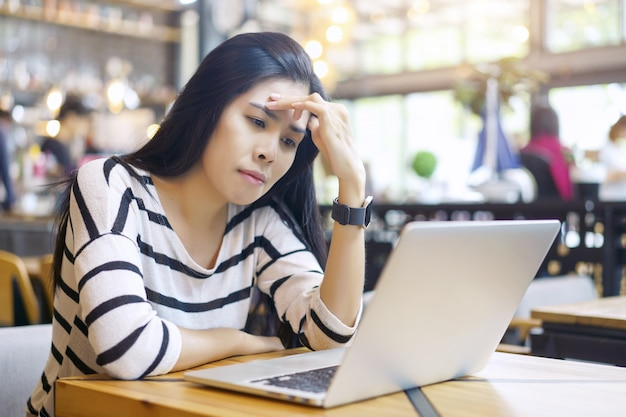 Serious and frustrated asian woman thinking of problem to working a difficult assignment in a desktop Premium Photo