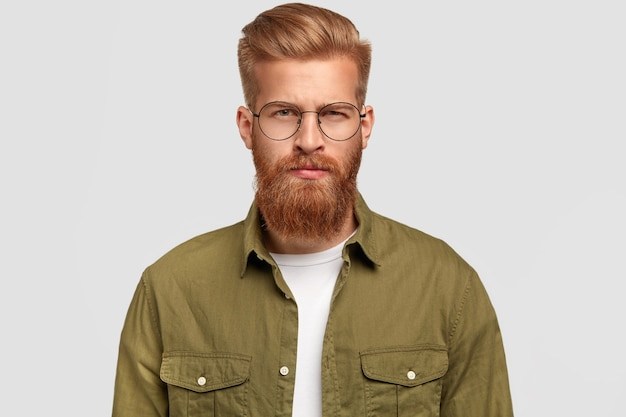 Serious ginger stylish man has thick beard and mustache, dressed in green shirt, looks seriously Free Photo