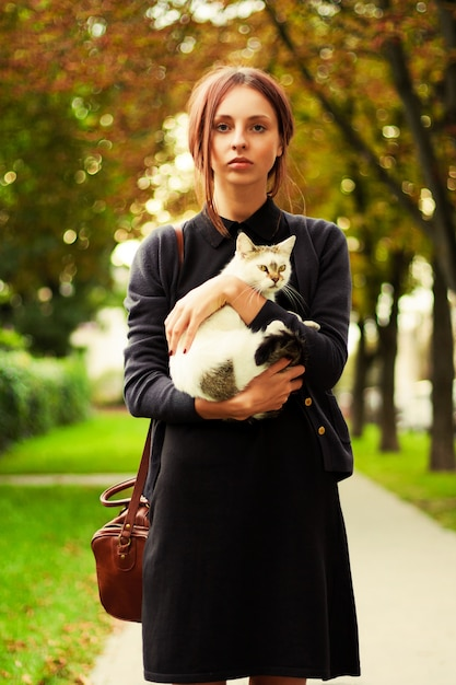 Serious girl hugging her cat in the park Free Photo