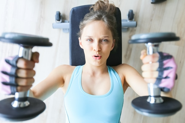Serious girl lying and lifting two dumbbells Free Photo