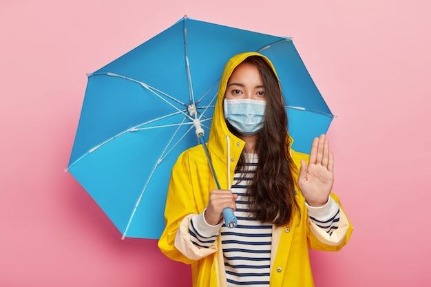La ragazza seria fa un gesto di arresto, chiede di non inquinare l'ambiente, cammina sotto la pioggia acida, indossa una maschera protettiva per ridurre gli inquinanti respiratori, indossa l'impermeabile, si nasconde sotto l'ombrellone Foto Gratuite