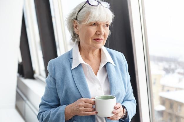 Grave imprenditrice matura dai capelli grigi con gli occhiali sulla sua testa ed eleganti abiti formali gustando un caffè caldo, in piedi dalla finestra con la tazza nelle sue mani, con sguardo pensieroso pensieroso Foto Gratuite