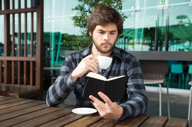 Serious guy excited with interesting book story Free Photo