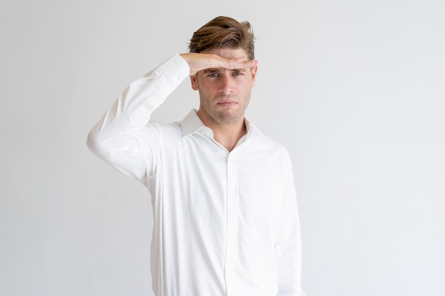Serious guy holding hand at forehead and looking into distance Free Photo