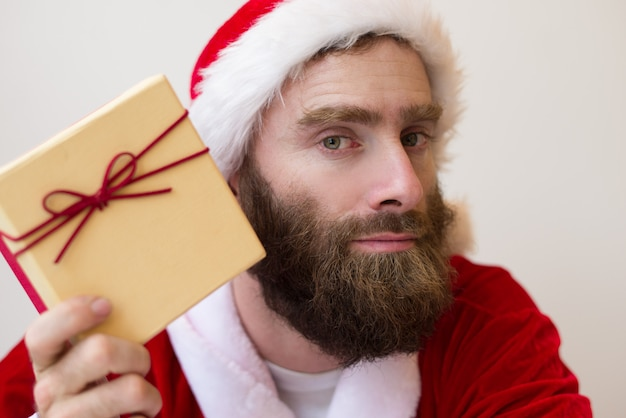 Serious guy wearing santa costume and holding gift box Free Photo